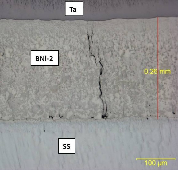 Figure 1.  Cross-section of braze joint between Ta and ferritic stainless steel using BNi-2 braze filler metal, showing a transverse crack in the braze filler metal.
